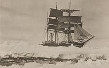 Three masted ship with sails spread, surrounded by pack ice, with a narrow lane of water in the foreground