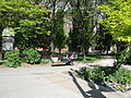 Homeless man sleeping on a park bench NW corner of Church and Queen.jpg