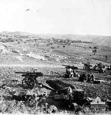 A battery of four artillery guns deployed in the field during fighting in the Judean Hills a week or so after the Battle of Mughar Ridge. The guns are surrounded by treeless hills and are firing at Ottoman positions which are out of the photo.