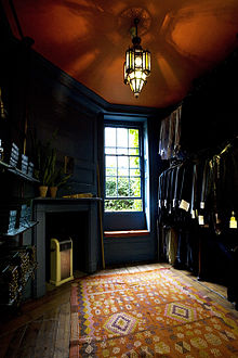 A wood panelled room, with polished wood floor, partly covered by a rug in the foreground. The room is lit by a gothic, stained glass ceiling light and from a single sash window. To the left of the window is a fireplace, with modern heater. The three shelves on the left wall are filled with shirtboxes. The right wall is hung with two rows of shirts and jackets, which have labels on their sleeves.