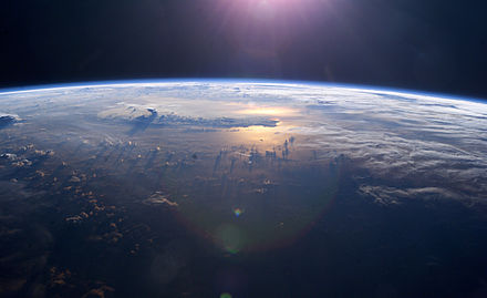 Sunset over the Pacific Ocean as seen from the International Space Station. Anvil tops of thunderclouds are also visible. Iss007e10807.jpg