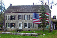 A large stone house with a large American flag draped across its upper right story behind an evergreen tree. In front of it is a blue and gfold historical marker.