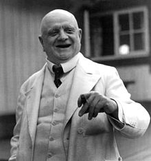 A jolly-looking older gentleman in a white suit, holding a cigar in his left hand and laughing