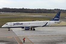 """Un aereo bianco con le parole """"jetBlue"""" dipinte sulla parte anteriore e una pinna caudale blu taxi in un aeroporto"""