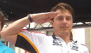 John Barrowman - Barrowman saluting in the style of Captain Jack Harkness from a float at the 2007 London Gay Pride parade.