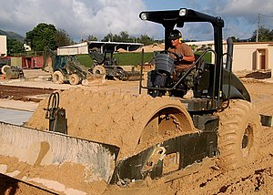 Road roller - Caterpillar soil compactor equipped with padfoot drum, being used to compact the ground before placing concrete