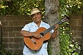 José-Luis Orozco playing guitar by tree.jpg