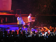 In a stage, two men, both wearing white shirts, can be seen holding microphones. The first man, wearing a long sleeve shirt, sings, while the other man, wearing a shirt, dances to the music played. A crowd of people can also be seen holding up their cellphones.