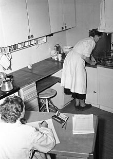 En kvinna arbetar i köket, en annan kvinna antecknar och klockar tiden (Rålambsvägen 8 och 10 i Stockholm)