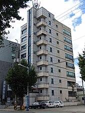 Davanti a un edificio beige di nove piani, tre auto parcheggiate