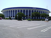 "A concrete building with the words ""Great Western Forum"" on top situates across an empty parking lot"