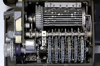 M-209 - An intermediate gear unit (center) meshes with gears adjoining each key wheel. Visible to the left of the image are the paper tape and typewheel that print out messages and ciphertext.