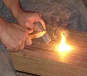Magnesium firestarter (in left hand), used with a pocket knife and flint to create sparks which ignite the shavings
