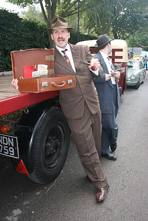 "Spiv - A man dressed as a spiv selling goods ""from the back of a lorry"" at a 2011 historical re-enactment, complete with look-out watching for the law"