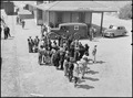 Manzanar Relocation Center, Manzanar, California. Evacuees of Japanese ancestry await bus for Manza . . . - NARA - 538489.tif
