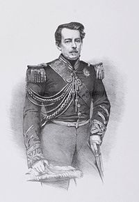 Lithograph of a drawing featuring a three-quarters length portrait of a middle-aged man with moustache wearing a military tunic with embroidered cuffs and decorated with epaulettes, lanyards, a sash of office and several medals and orders at his neck, and holding a feathered bicorne hat in his right hand