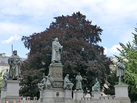 Luther Monument in Worms. His statue is surrounded by the figures of his lay protectors and earlier Church reformers including John Wycliffe, Jan Hus and Girolamo Savonarola. Martin-Luther-Denkmal, Worms.JPG