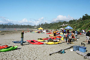 Photo of beach, with several kayaks strewn around and people in background