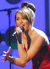 A three-quarter view of a female teen who faces left and leans slightly forward while singing into a black microphone: She wars a red ball gown and her straight brown hair is styled in a large bun.