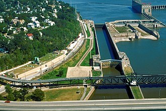 Lock and Dam No. 19 - Aerial view of the locks at Lock and Dam 19. The 1957 lock is the largest at left, with the dewatered drydock and 1913 lock at its right. The old Keokuk Rail Bridge and Keokuk-Hamilton Bridge are visible in the foreground. View is upriver to the northeast.