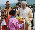 Narendra Modi blessing a Bhutanese girl child, who presented a bouquet, before his departure from Bhutan, in Thimphu, on June 16, 2014. The Prime Minister of Bhutan, Mr. Lyonchhen Tshering Tobgay is also seen.jpg