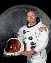 man in spacesuit holding helmet, large image of the moon in the background