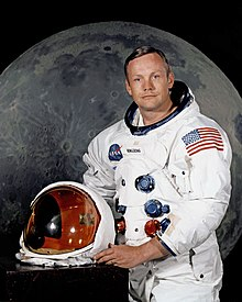 A light-skinned man in his late 30s, with blue eyes and brown hair parted to the right. He wears a white space suit, and holds the helmet. The space suit has five hose connectors on the front. There is a large U.S. flag on the left shoulder. The helmet's transparent faceplate is tinted gold.