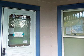 Foreclosure - Notices accumulate on the door and window of a foreclosed, unoccupied house.