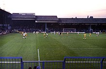 A football match in progress at a modest, traditional British football ground.
