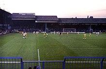 Идет профессиональный футбольный матч, вид из-за ворот.  Одна команда в белом, а другая в желтом.