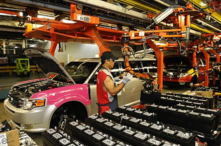 A worker at the Oakville Assembly installs a battery in an automobile. The automotive industry is a contributor to the economy of Ontario. Oakville Assembly.jpg