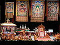 On the stage, HH the Dalai Lama, HH The Karmapa (wearing red deity hat signifying red secret bodhicitta), thangkas, Kalachakra pavilion, monks, nun, formal robes, Kalachakra for World Peace, Washington D.C., USA.jpg