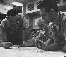 Three naval officer plotting the submerged course of the nuclear submarine Triton, with Captain Beach seated before chart in the center, with Lt. Commander Will M. Adams standing at right holding a pair of dividers and Lt. Commander Robert W. Bulmer standing at the left holding a pencil, and an unidentified individual seated in the background.