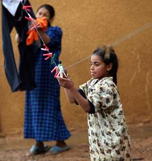 Refugees of Iraq - Palestinian Iraqi girl plays with a clothesline
