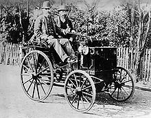 Photo d'une voiture d'apparence hippomobile avec un chauffeur et un passager.