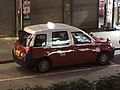 Parked Toyota Comfort Hybrid red taxi.jpg