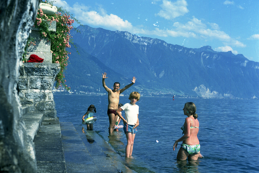 People bathing in Lake Geneva, Vaud Canton, with Jura Mountains in background, 1968