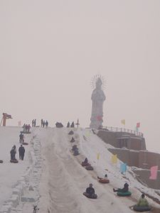 People sporting in snow by a statue of goddess Guanyin in Wujiaqu, Xinjiang