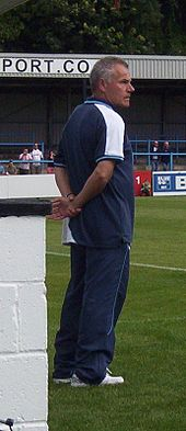 A middle-aged man with greying hair, wearing a dark blue T-shirt and matching jogging bottoms, standing near the touchline of a sports pitch.  Some spectators are visible in the background.