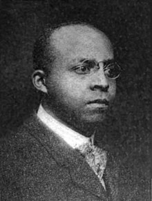 An African-American man with close-cut hair wearing glasses, a black jacket, light shirt, and patterned tie
