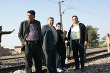 Four people standing next to a railroad track