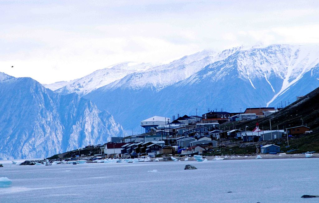view of the town of Pond Inlet covered in snow ahead of mountains, Nunavut, Canada