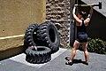 Pratiquante de CrossFit, faisant l'exercice de frappe sur pneu.jpg