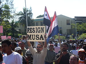 2005 Belize unrest - Crowds outside the National Assembly, with signs calling for the resignation of Prime Minister Said Musa.