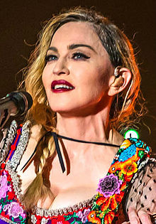 A closeup photo of Madonna with braided hair, heavy makeup and a colorful, low-cut blouse.