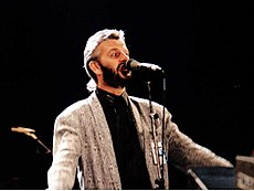 Starr in his forties, wearing a grey jacket and a black shirt, standing behind a microphone and singing.