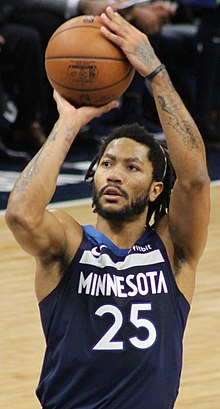 Hip length view of man raising the basketball to shoot free throw, with black moustache, beard, and short dreadlocks, thin white headband, wearing navy blue Timberwolves uniform