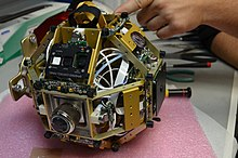 A SPHERES satellite without the plastic shell. Aluminum structure, a control panel, ultrasonic sensors, thrusters, pressure regulator knob and pressure gauge are visible.