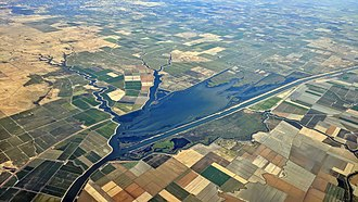 Sacramento Deep Water Ship Channel - Aerial view of the Sacramento River Deep Water Ship Channel and some adjoining and nearby sloughs and farm country.  Dixon and Davis are visible in the distance.