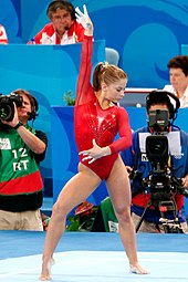 A female gymnast in a red leotard, looking down and to her left, with her right hand raised and her left hand across her waist.  In the background sit a number of people including a cameraman, a photographer, a commentator and a judge.